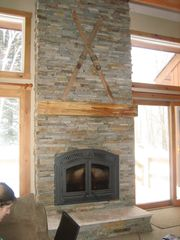 Jay Peak condo photo - New wrought iron wood fireplace with 14' stone hearth, watch Tram out windows!