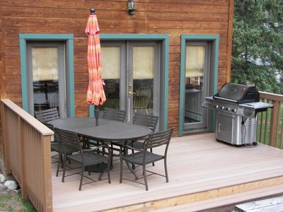 Deck off of dining room with gas grill and deck furniture.