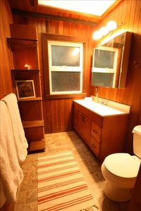 Bathroom complete with cedar lined walls and walk-in shower.