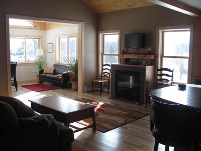 View of the living room with gas fireplace, looking into sunroom / dining room!