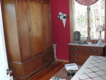 Guest bedroom with queen bed and antique furnishings.