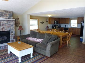 Open floor plan. Living room, dining area and kitchen. Stone fireplace.