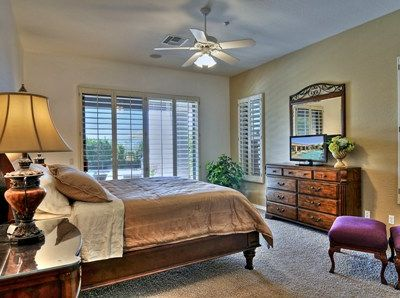 Master Bedroom w/king bed, TV, calif shutters, steps out to covered patio & s/pool.