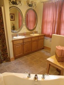 Master bath has walk-in shower, double vanity sinks, & privacy wall for toilet.