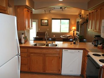 A large kitchen that is fully stocked from cookware, dishware and even coffee +!