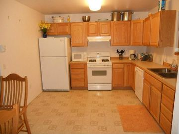 Soldotna house rental - Kitchen with large dining table opens into living area.