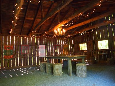 former wagon barn converted to creekside dining pavillion with large farm table