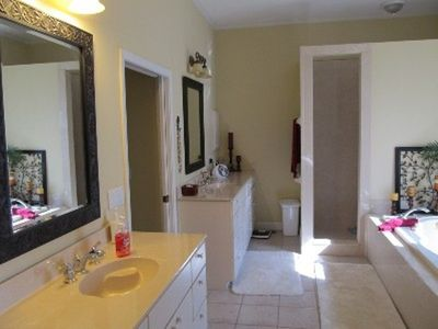 Master bathroom with his/her sinks, garden tub, walk in shower