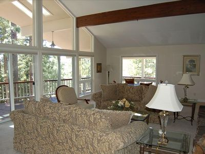 Spacious living room with vaulted ceilings and a wall of windows