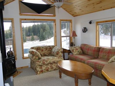 Living Room with gas stove and cozy seating. Open to the kitchen.
