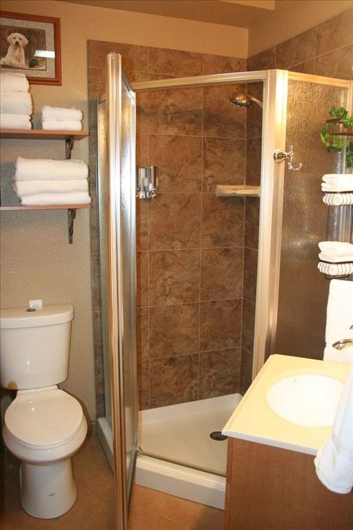 Second bathroom w/ tile shower and glass doors with massage wand shower head!