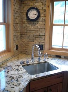 Gourmet kitchen with slab granite, custom tile, & stainless steel appliances!