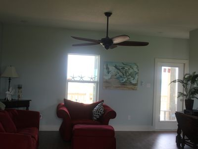 Living room with large ceiling fan, large TV, open to Kitchen