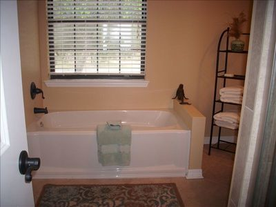 Master bathroom with separate tub, tiled shower, enclosed toilet, walk-in closet