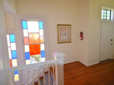 Original wood floors, stained glass windows and posts at the top of the stairs.