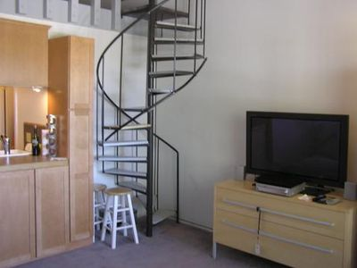 spiral staircase from living area leads to bedroom loft