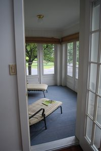 Laconia condo rental - Screened in porch with two lounge chairs.
