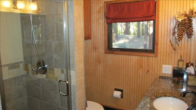 Master Bath- Granite counters and custom tile step in shower. Views of  forest!