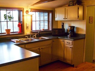 Spacious updated kitchen overlooks the wooded back yard