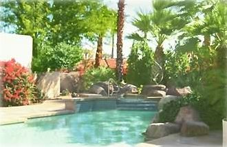 Boulders, mature palms and Bougainvillea surrounds spa and pool