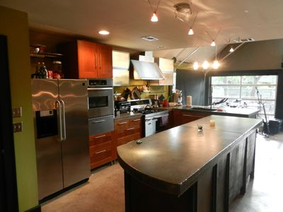 Kitchen. Concrete countertops, stainless appliances, gas stove, ice machine.