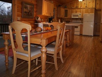 Dining area, bar, full kitchen. Table seats 8. Warm wood adds rustic charm.