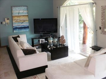 Playa del Carmen condo rental - Living area with entertainment center and large balcony overlooking the pool