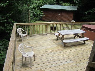 Partial view of lower deck with hot tub leading to level yard and play room