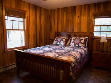 2nd bedroom w/ queen bed and fine wood furnishings and paneling.