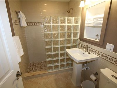 One of two glass block pebble floor showers and bath