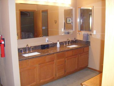 Double sinks, and long granite counters, with good lighting and mirror above.