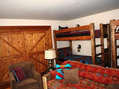 Downstairs bunk room with stone fireplace, pull out sofa bed, and flat screen TV