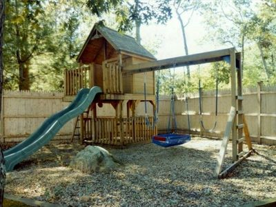 Wooden play swingset with up and down clubhouse and baby rocket swing.