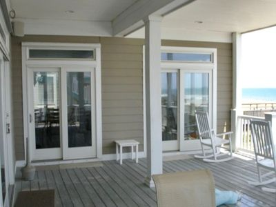 Oceanfront dining room beside porch with rockers