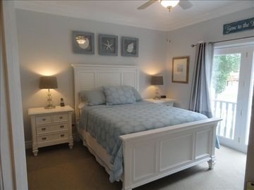 Beautiful master suite with queen bed, adjoining bathroom and view of lake