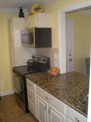 St. Simons Island condo photo - Full size range and microwave with large countertop to work on or gather around.