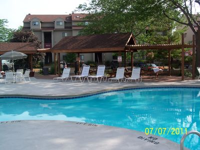 pool area with chairs, picnic tables, gas grills. Hot tub further left.
