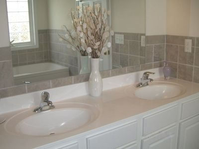 Huge master bath with whirlpool tub, double sinks, and stall shower
