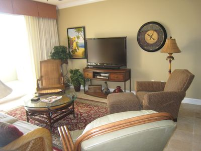 Living room adjoins the balcony, has a large HDTV, recliner & a view of the Gulf
