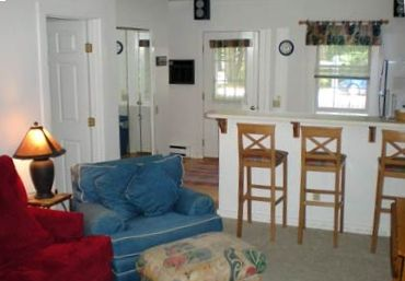 View of the cozy living area looking into the fully-stocked kitchen