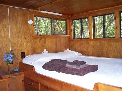 A queen size bed and a view out into the woods