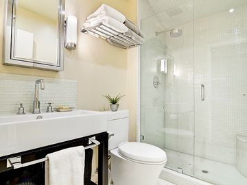Master bathroom with huge glass-tiled shower with bench