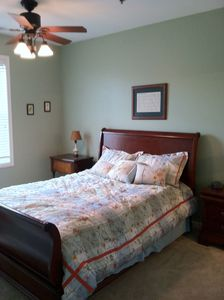 A queen sized bed and ceiling fan in the Master Bedroom