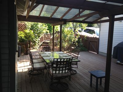 Comfortable shaded outdoor dining -- gas grill and rose garden view.