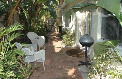 Terrace by front door is tropically landscaped, w/ electric grill.