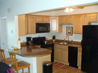 Weirs Beach condo photo - Updated kitchen with microwave, stove, dishwasher, coffee pot, toaster, fridge