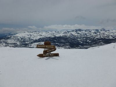 Top of the world with snow burying a 15 foot sign