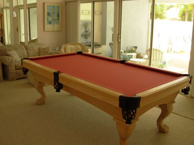 Full size billiard table in den, with view of pool