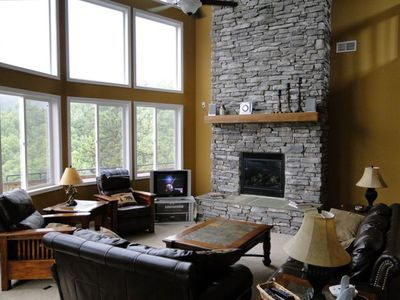 Great Room with wall of windows and massive stone fireplace - leather seating