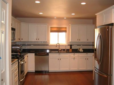 Kitchen with recessed lighting and all stainless steel appliances.